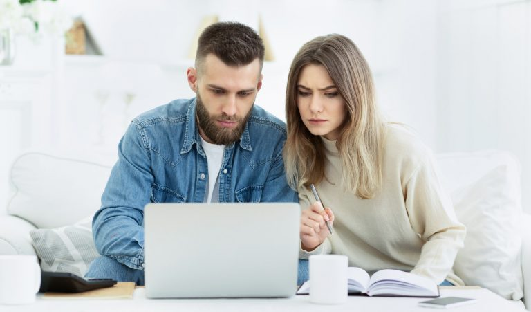Young couple planning family budget with laptop